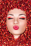 Beautiful woman lying in wild strawberry. And air kiss Stock Images
