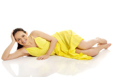 Beautiful woman lying in yellow dress. Stock Photography
