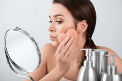 Beautiful woman make a facial treatment with a sponge in the mirror. Woman make a facial treatment with a sponge in the mirror Royalty Free Stock Photos