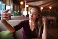 Beautiful woman make selfie in restaurant. Royalty Free Stock Photo