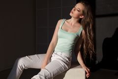 Beautiful woman with make-up and hairdo sitting in the bright clothes Stock Photo