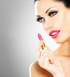 Beautiful woman applying pink lipstick on lips Stock Images