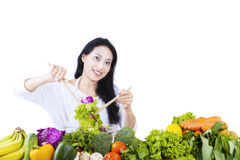 Beautiful woman makes salad on white Royalty Free Stock Photography