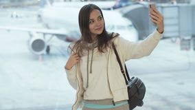 Beautiful woman makes selfie photo near airport window in background of airplane. Girl in white jacket with backpack uses smartphone in airport lounge. Concept stock video