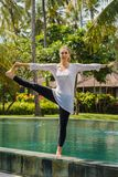 Beautiful woman makes yoga practice, meditation, stretching leg in standing pose on the edge of swimming pool in resort stock images