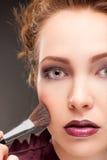 Beautiful woman with makeup brush Royalty Free Stock Photos