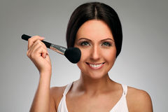 Beautiful woman with makeup brush Royalty Free Stock Photo