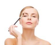 Beautiful woman with makeup brush Stock Image