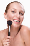 Beautiful woman with makeup brush Stock Images