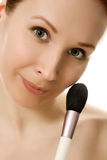Beautiful woman with makeup brush near her face Stock Photos