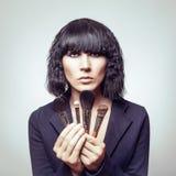 Beautiful woman with makeup brushes Royalty Free Stock Photos
