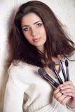 Beautiful woman with makeup brushes Stock Photo