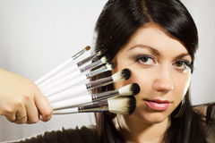 Beautiful woman with makeup brushes Royalty Free Stock Photo