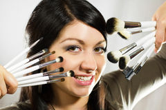 Beautiful woman with makeup brushes Stock Image