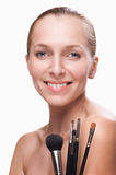 Beautiful woman with makeup brushes Stock Photos