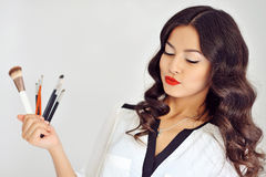 Beautiful woman with makeup brushes near her face Stock Photography
