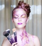 Beautiful woman with makeup brushes near Royalty Free Stock Photography