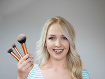 Beautiful woman with makeup brushes near her face Stock Image