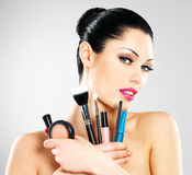 Beautiful woman with makeup brushes Stock Photography