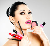Woman with makeup cosmetic tools near her face. Royalty Free Stock Photos