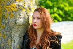 Cute glamorous girl standing against a tree looking to the left royalty free stock photo