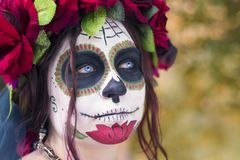 Beautiful woman in makeup traditional Mexican Calavera skull Katrina in the autumn forest, in a wreath of red flowers. Day of the. Dead. Halloween celebration royalty free stock images