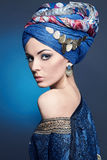 Beautiful woman.makeup.turban. Portrait of young beautiful woman close up. Perfect makeup. Perfect skin. Fashion photo.Beauty lady with colored turban over blue Royalty Free Stock Photography