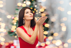 Beautiful woman making christmas wish over lights. People, holidays and christmas concept - beautiful sexy woman in red dress making wish over lights background Stock Photo