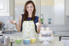Beautiful woman making cupcakes. Cute young woman decorating some cupcakes royalty free stock images