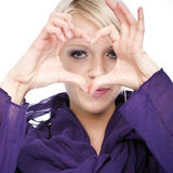 Beautiful woman making a finger heart sign. Beautiful young blond woman making a romantic heart sign with her fingers in front of her face isolated on white Stock Image