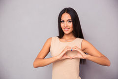 Beautiful woman making heart with fingers Stock Photo