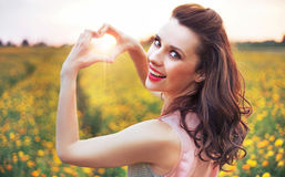 Beautiful woman making a heart sign Stock Images
