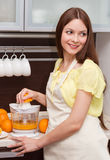 Beautiful woman making orange juice. In modern kitchen Royalty Free Stock Photos