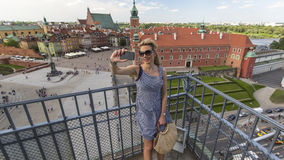 Beautiful  woman making selfie with phone on the background Warsaw Castle Square. Royalty Free Stock Photography