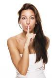 Beautiful woman making shush sign. Beautiful brunette woman making shush sign on white background Royalty Free Stock Image