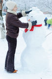 Beautiful woman making snowman Stock Images