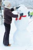 Beautiful woman making snowman Stock Images