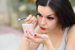 Beautiful woman making up eyelashes herself Royalty Free Stock Photo