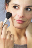 Beautiful woman making up her face Stock Image