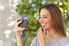 Beautiful woman making up using a smart phone as a mirror. With a green background Stock Photo