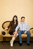 Beautiful woman and man sitting on sofa in room Stock Image