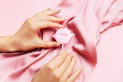Beautiful woman manicure on creative pink background with silk fabric. Minimalist trend. Beautiful woman manicure on creative trendy pink background with silk stock photo