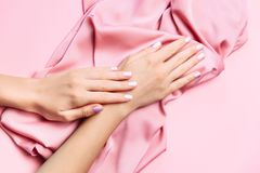 Beautiful woman manicure on creative pink background with silk fabric. Minimalist trend. Beautiful woman manicure on creative trendy pink background with silk royalty free stock images