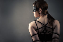 Beautiful woman in mask and bondage. Isolated on gray background Stock Images