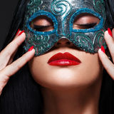 Beautiful woman with mask. Red Sexy Lips and Nails closeup. Sensual mouth. Manicure and Makeup. Make up concept. Passion Royalty Free Stock Photo