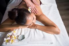 Beautiful woman massage in spa. Young Asian beautiful tanned woman in spa club. Body care treatment by Thai oil. Cute girl having hands massage at back by Stock Images