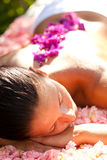 Beautiful woman on the massage table. Beautiful woman relaxing on the massage table covered by flowers stock photo