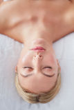 Beautiful woman on a massage table at dayspa. Top view shot of beautiful young caucasian woman lying with her eyes closed on a massage table at dayspa Royalty Free Stock Photo