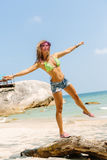 Beautiful woman with mat in tropics. Beautiful fit woman in bikini, jeans shorts and transparent cap balancing on old tree at the tropical beach. Summer Royalty Free Stock Photo