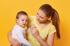 A beautiful woman on maternity leave and her cute little daughter hug each other on bright yellow background. A sweet child looks. With interest aside. Family royalty free stock photography